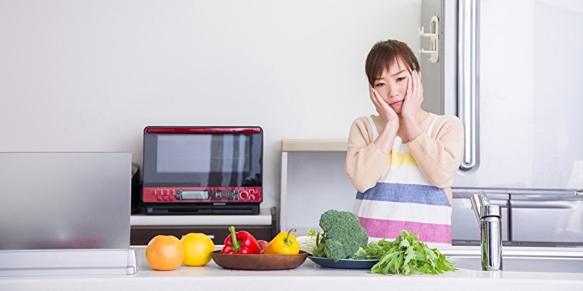 キッチンで悩む女性